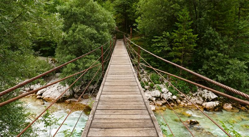 Houten hangbrug over turkooise rivier stock fotografie