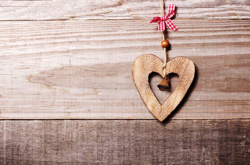 Houten hart met klokdecoratie op uitstekende eiken achtergrond, kuuroord stock foto's