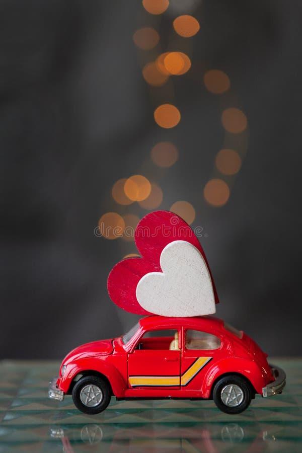 Houten Hart op het dak van de uiterst kleine stuk speelgoed rode auto Sluit omhoog op bokehachtergrond royalty-vrije stock afbeelding