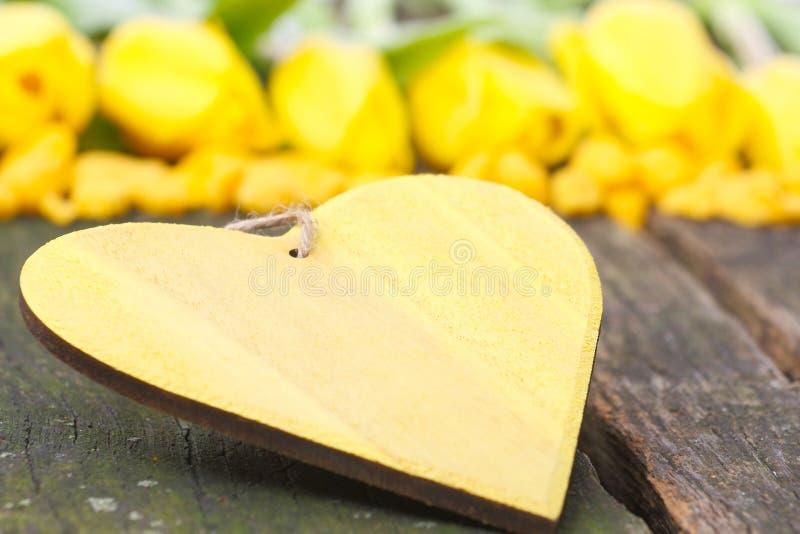 Houten hart van gele tulpen stock fotografie