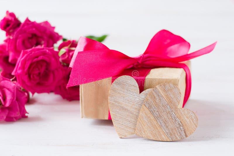 Houten harten, geschenk met roze boog, roze roze rozen stock fotografie