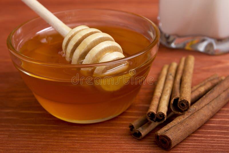 Houten honingsstok en pijpjes kaneel royalty-vrije stock afbeeldingen