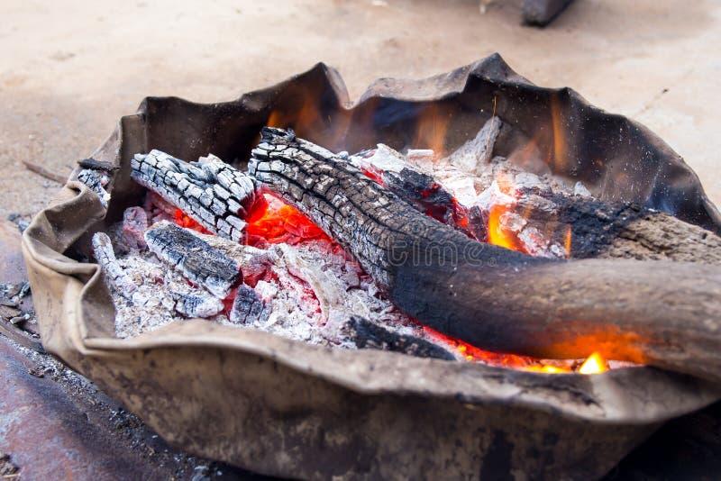 Houten houtskoolbrand op het oude bassin, dorpsbewoner het ontsteken aan relie royalty-vrije stock foto's