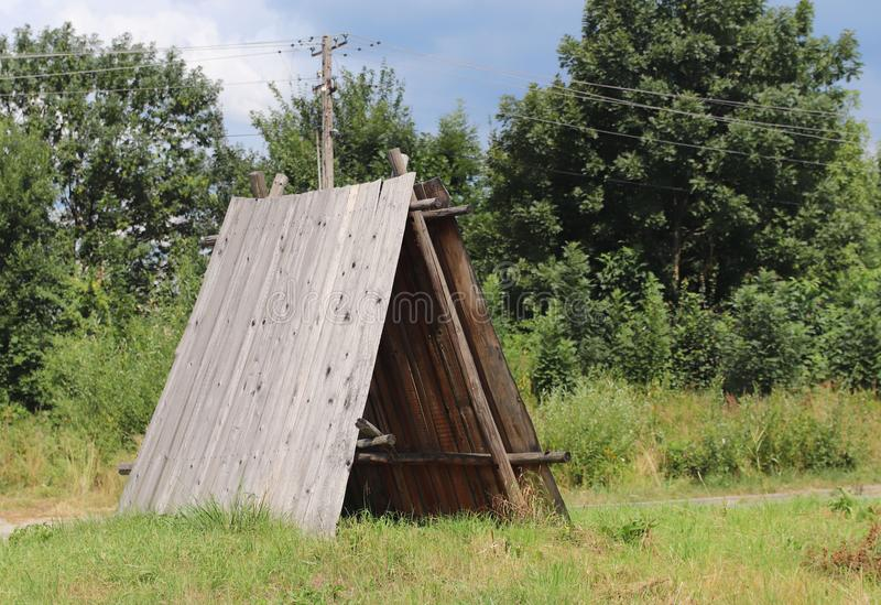 Houten hut in green voor een vakantie in de stijging Primitieve schuilplaats van regen en zon voor verkenners, jagers en herders  royalty-vrije stock afbeeldingen