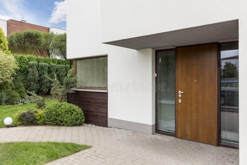Houten ingangsdeur aan modern huis stock afbeelding