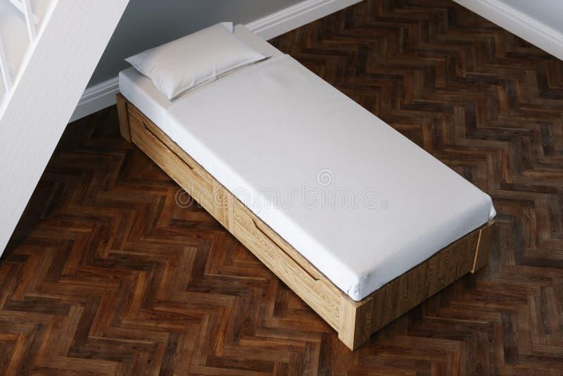 Houten jong geitjebed in nieuwe kindruimte onder houten treden stock foto