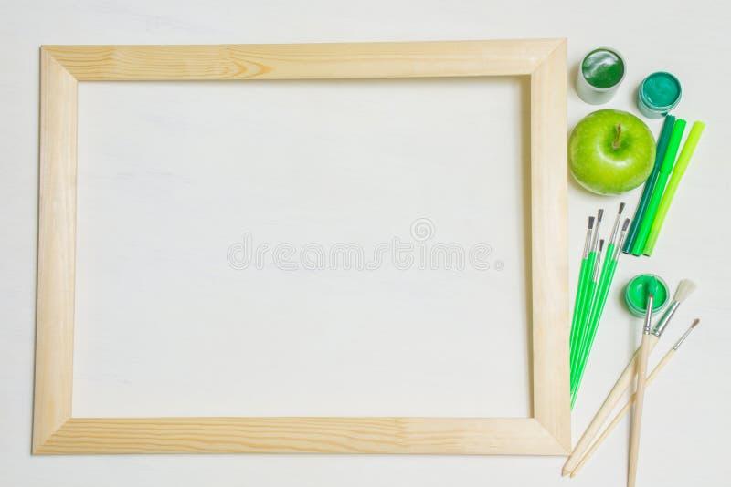 Houten kader met penselen en groene appel royalty-vrije stock fotografie