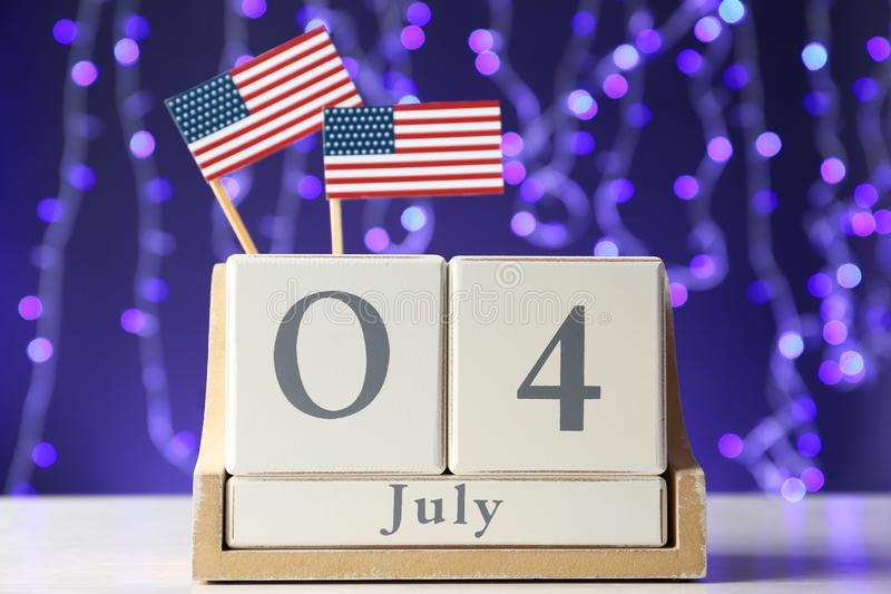 Houten kalender met de vlaggen van de V.S. op lijst tegen vage lichten, close-up Gelukkige onafhankelijkheid stock fotografie