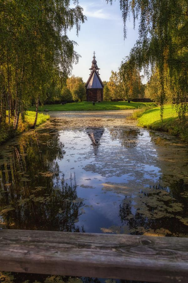 Houten kapel op de bank van een overwoekerde vijver, Kostroma, Rusland stock afbeelding
