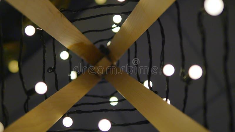 Houten Kerstboom Slinger van lichten Uitstekende stijl Achtergrond van gloeilampen in een gebied in rust het vertroebelen stock fotografie