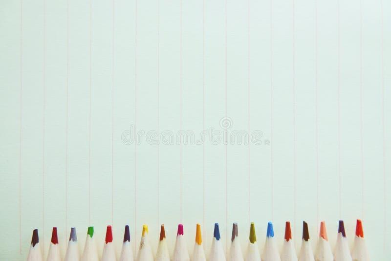 Houten kleurrijke potloden op een notitieboekjedocument achtergrond stock afbeelding