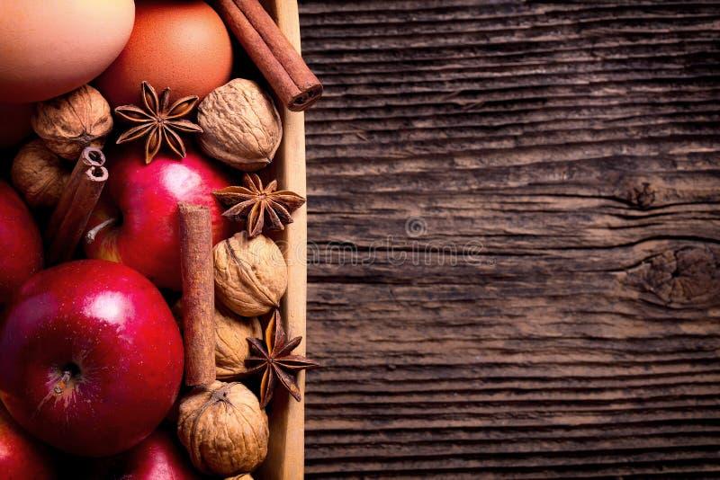 Houten kom met appel, eieren en okkernoot stock afbeelding
