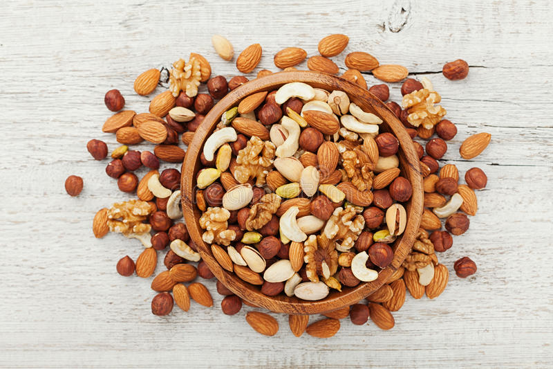 Houten kom met gemengde noten op de witte mening van de lijstbovenkant Gezonde voedsel en snack Okkernoot, pistaches, amandelen,  stock afbeeldingen
