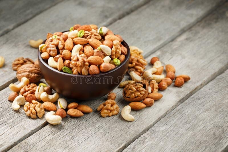 Houten kom met gemengde noten op een houten grijze achtergrond Okkernoot, pistaches, amandelen, hazelnoten en cachou, okkernoot royalty-vrije stock foto's