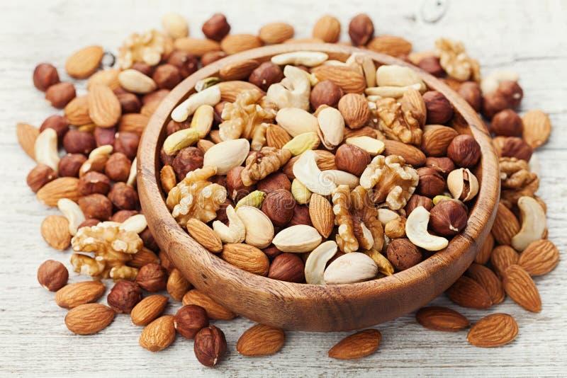 Houten kom met gemengde noten op witte lijst Gezonde voedsel en snack Okkernoot, pistaches, amandelen, hazelnoten en cachou stock afbeeldingen