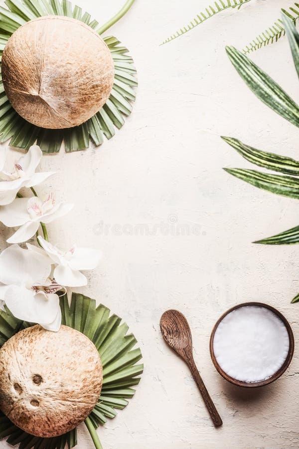 Houten kom met kokosnotenolie en lepel op lichte achtergrond met kokosnoten, tropische bladeren en bloemen Natuurlijk organisch c royalty-vrije stock foto's