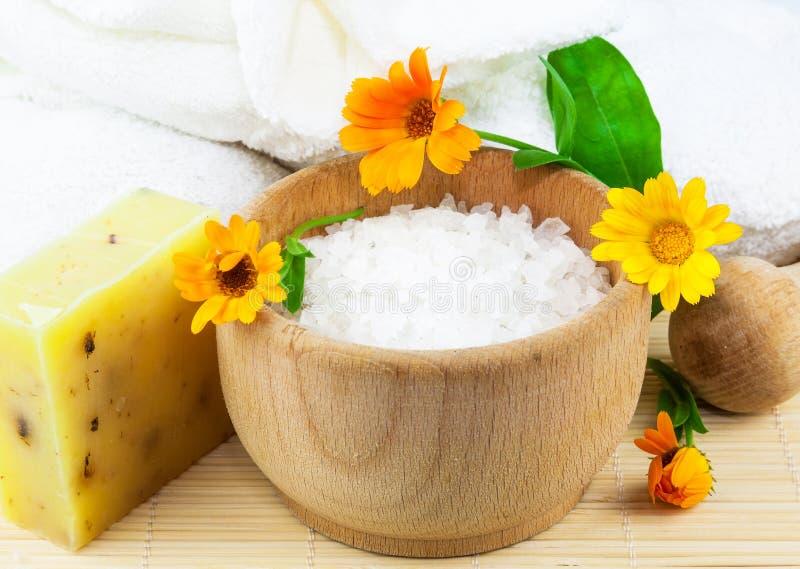 Houten kom met overzeese zout, zeep, handdoeken en goudsbloemen stock afbeelding