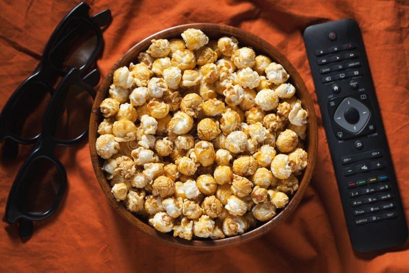 Houten kom met zoete popcorn, TV-afstandsbediening en 3D glazen op oranje beddegoed Hoogste mening Snacks en voedsel voor een fil stock fotografie
