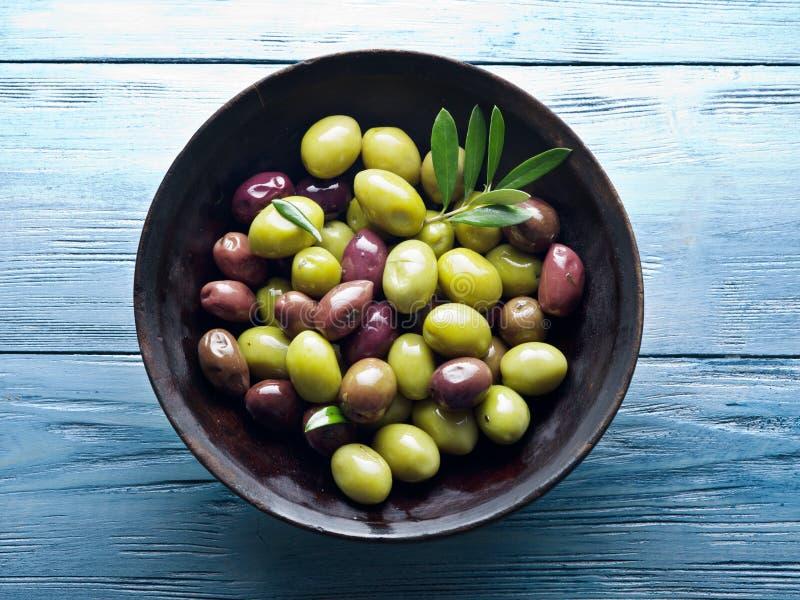 Houten komhoogtepunt van olijven en olijftakjes royalty-vrije stock afbeelding