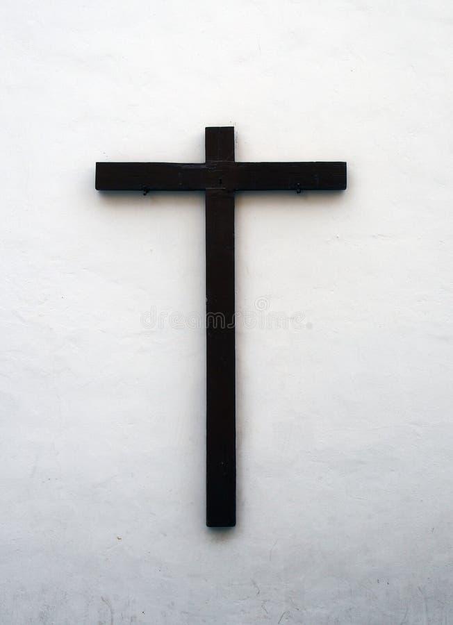 Houten kruis op een buiten witte muur in Spanje stock foto