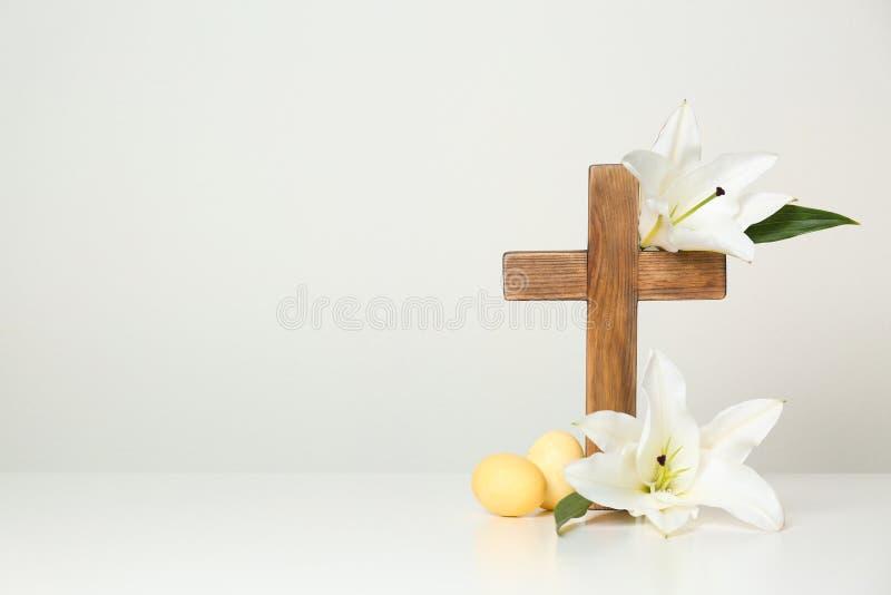 Houten kruis, paaseieren en bloesemlelies op lijst tegen lichte achtergrond royalty-vrije stock fotografie