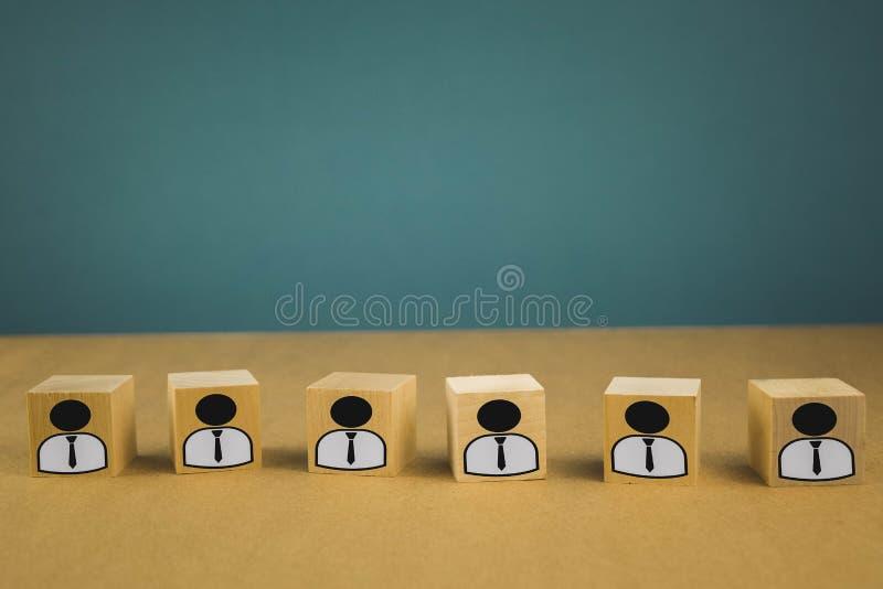 houten kubussen die, loonarbeiders zich op een rij bevinden die betekenen die zich in één lijn, abstractie op een blauwe achtergr stock fotografie