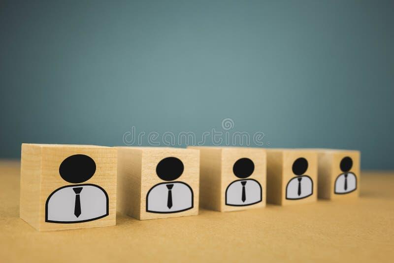 houten kubussen die, loonarbeiders zich op een rij bevinden die betekenen die zich in ??n lijn, abstractie op een blauwe achtergr stock afbeeldingen