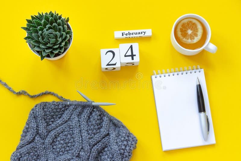 Houten kubussenkalender 24 Februari Kop thee met citroen, lege open blocnote voor tekst Pot met succulente en grijze stof  stock afbeelding
