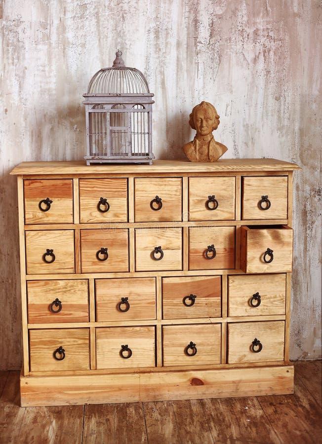 Houten ladenkast in sjofele gestileerde ruimte met vogelkooi en royalty-vrije stock fotografie