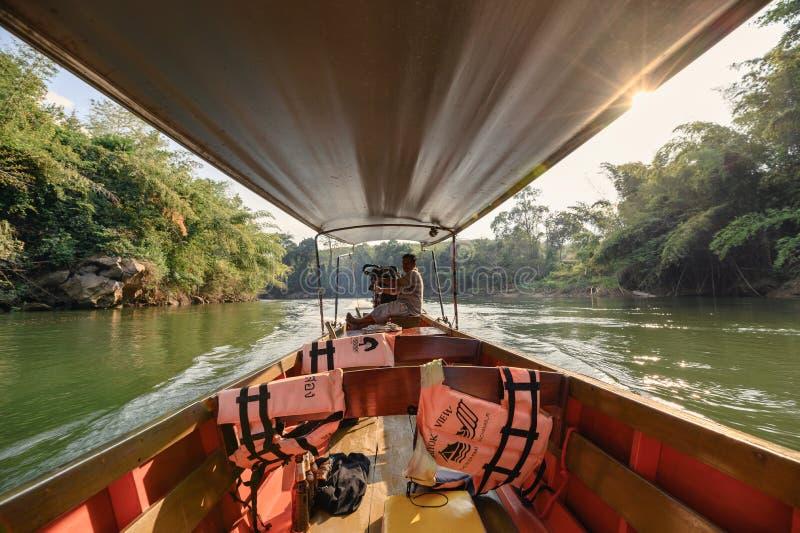 Houten lang-staartboot die in tropisch regenwoud op rivierkwai varen stock fotografie
