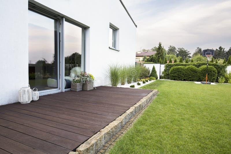 Houten leeg terras van wit huis met groene gras en bomen Echte foto stock foto