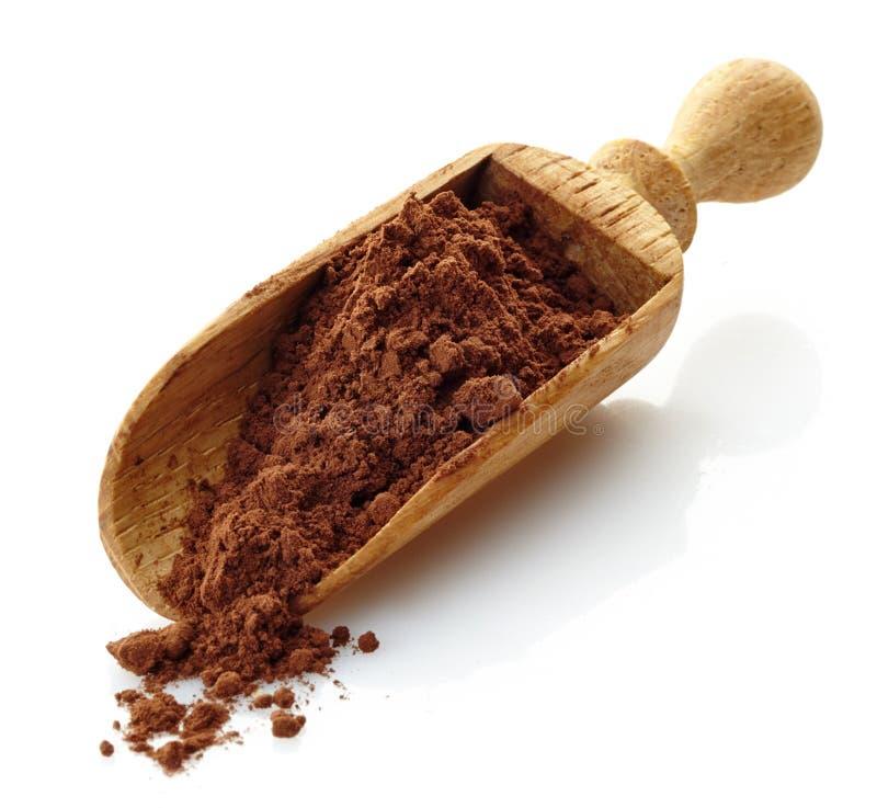 Houten lepel met cacaopoeder stock afbeelding