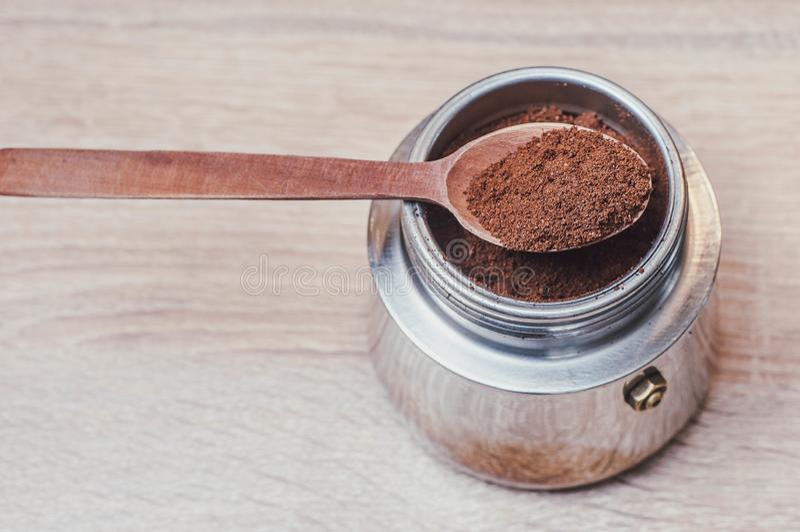 Houten lepel met gebrouwen koffie in een koffiezetapparaat en prettige tint als energiebron na slaap stock foto
