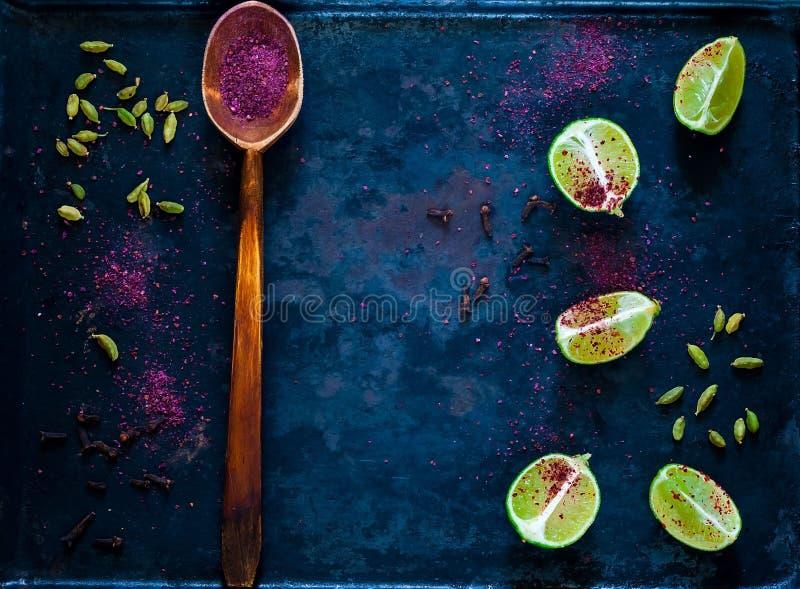 Houten lepel met kruid sumac en citrusvruchtenkalk op uitstekende roestige metaalachtergrond, ingrediënten voor salades, hoogste  stock foto's