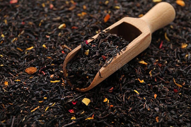 Houten lepel op droge zwarte theebladen stock afbeelding