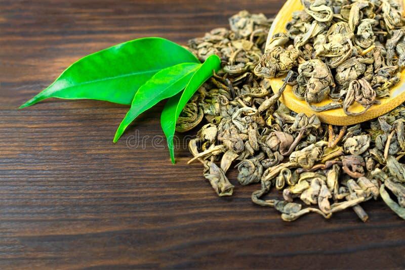 Houten lepel van droge thee met groene theebladen op darkbackground stock afbeelding