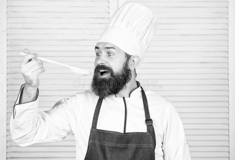 Houten lepel vegetari?r Rijpe chef-kok met baard Gebaarde mensenkok in culinaire keuken, Chef-kokmens in hoed Geheime smaak stock afbeeldingen