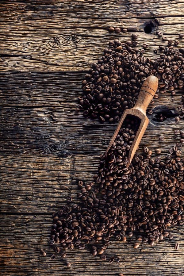 Houten lepelhoogtepunt van koffiebonen op oude eiken lijst royalty-vrije stock afbeelding