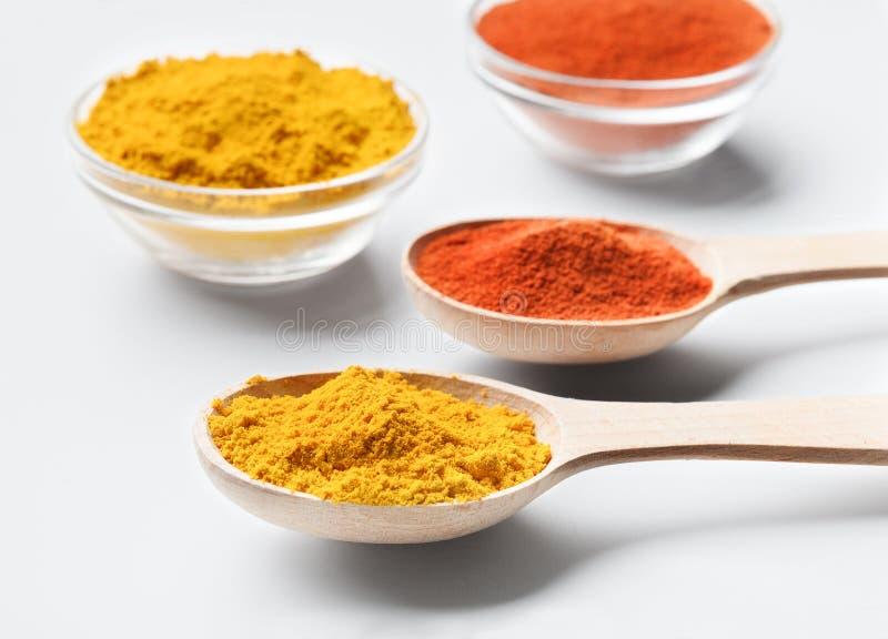Houten lepels en kommen met paprika en kurkumapoeder op wit stock afbeelding