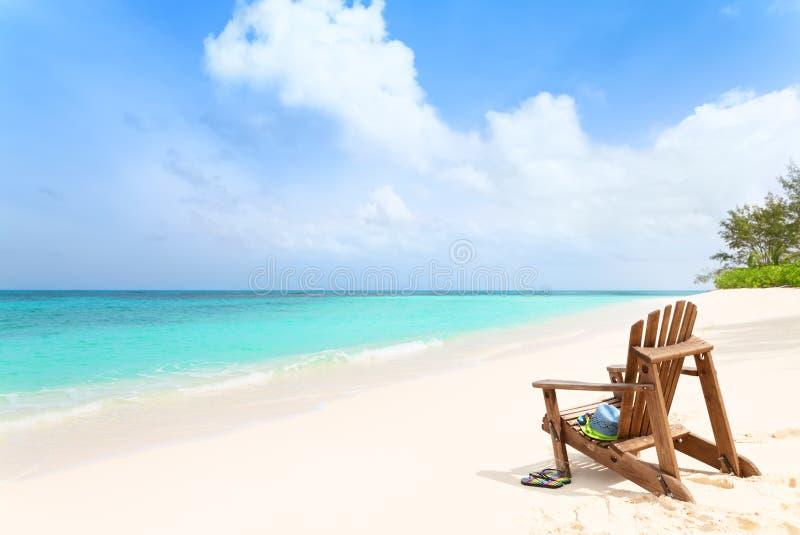 Houten ligstoel met hoed en pantoffels bij tropisch strand, samenvatting royalty-vrije stock foto's