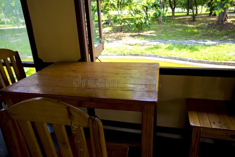 Houten lijst en stoelen gezet naast de vensters Het zonlicht is glanst op de lijst en voorzit maakt comfortabele streek en ontspa royalty-vrije stock afbeeldingen