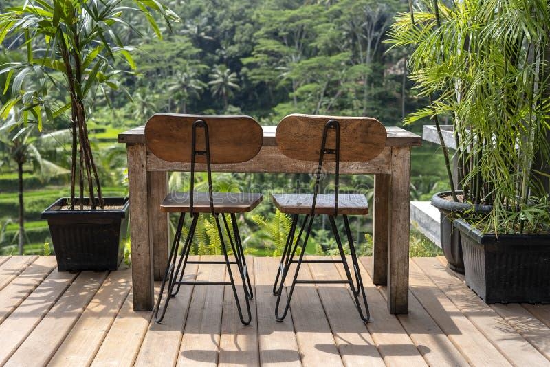 Houten lijst en stoelen in lege tropische koffie naast rijstterrassen in eiland Bali, Indonesi? stock afbeelding
