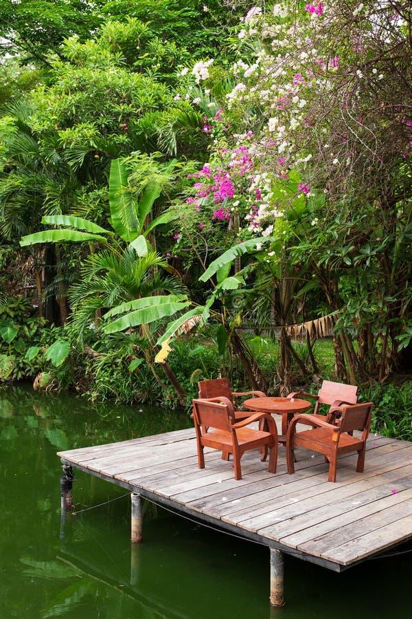 Houten lijst en vier stoelen op een platform op een meer in tropische wildernis royalty-vrije stock afbeeldingen