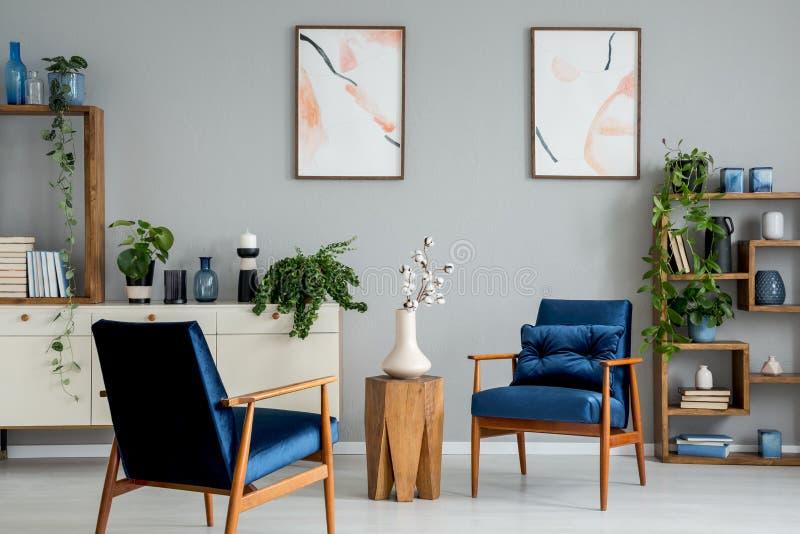 Houten lijst met bloemen tussen blauwe leunstoelen in grijs binnenland met affiches en installaties royalty-vrije stock fotografie