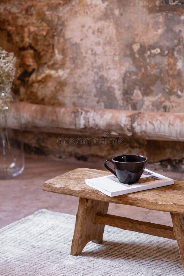Houten lijst met boek en kop op wit tapijt in eenvoudig woonkamerbinnenland met installatie royalty-vrije stock afbeelding
