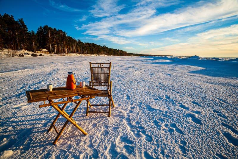 houten lijst met koffie op sneeuwstrand door het overzees royalty-vrije stock foto