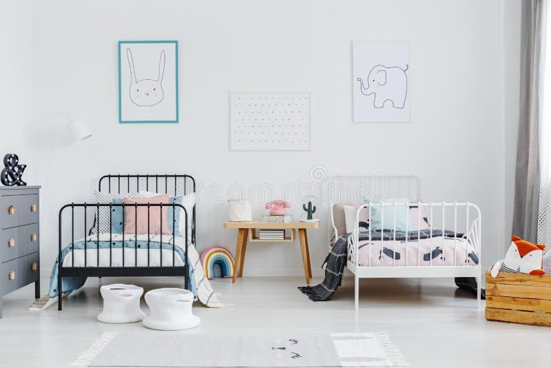 Houten lijst tussen zwart-wit bed in kinderenslaapkamer int. stock fotografie