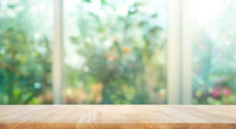 Houten lijstbovenkant bij het onduidelijke beeld van venster met de achtergrond van de tuinbloem stock fotografie