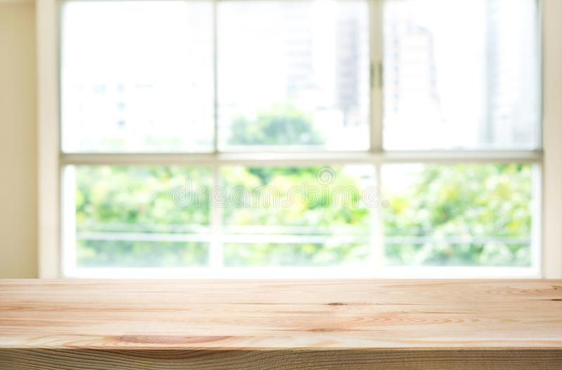 Houten lijstbovenkant bij het onduidelijke beeld van vensterglas en abstracte groene tuin stock foto's