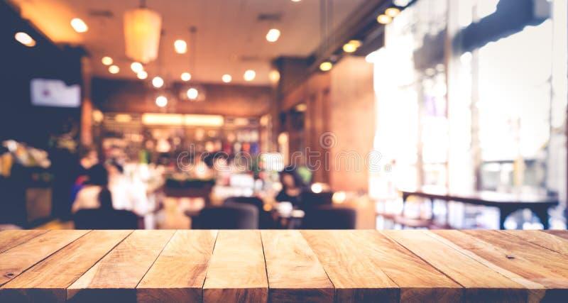 Houten lijstbovenkant met onduidelijk beeld van mensen in koffiewinkel of koffie, restaurant stock afbeeldingen